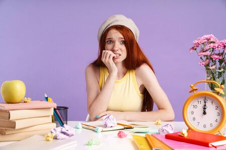 Photo of stressed student girl biting her nails while sitting at desk on lesson with exercise books isolated over purple background