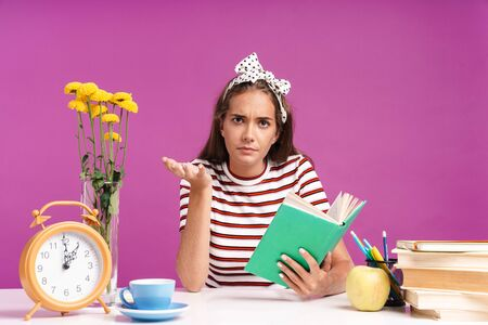 Attractive confused young girl sitting at the desk isolated over pink background, doing homework, holding opened book