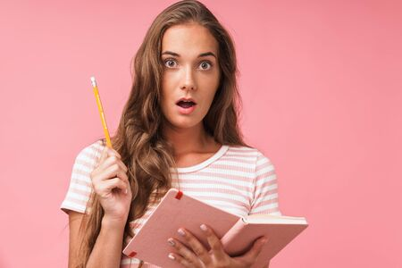 Image closeup of beautiful surprised woman wearing striped t-shirt looking at camera while holding diary and pencil isolated over pink wall Banco de Imagens