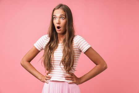 Image closeup of surprised beautiful woman expressing wonder with big eyes while standing with arms at waist isolated over pink background
