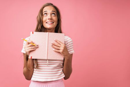 Image of amazed pretty woman wearing striped t-shirt looking upward while holding diary and pencil isolated over pink wall Banco de Imagens