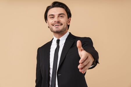 Portrait of a handsome smiling young businessman wearing suit standing isolated over beige background, outsretched hand for greeting