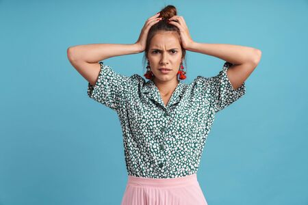 Portrait of a lovely confused young woman wearing shirt and bright earrings standing isolated over blue background, shrugging shoulders