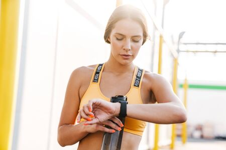 Image of attractive woman in sportswear holding water bottle and looking at wristwatch outdoors
