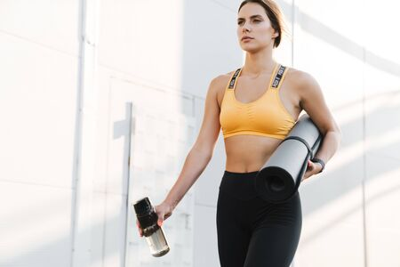Image of lovely woman in sportswear walking with yoga mat and water bottle outdoors