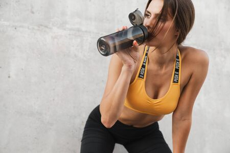 Image of athletic woman in sportswear drinking water from plastic bottle while standing over concrete wall outdoors