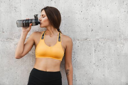 Image of fitness woman in sportswear drinking water from plastic bottle while standing over concrete wall outdoors