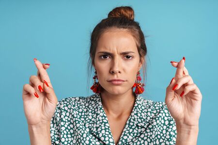 Close up portrait of a lovely worried young woman wearing shirt and bright earrings standing isolated over blue background, holding fingers crossed for good luck Banque d'images