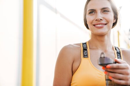Image of fitness woman in sportswear holding water bottle while walking outdoors in sunny morning