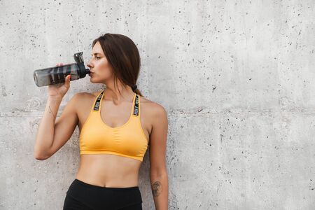 Image of slim woman in sportswear drinking water from plastic bottle while standing over concrete wall outdoors