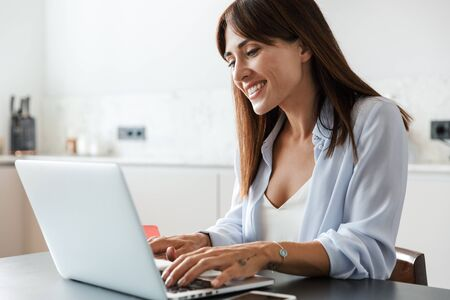 Photo d'une jeune femme joyeuse et heureuse à l'intérieur à la maison dans la cuisine à l'aide d'un ordinateur portable. Banque d'images