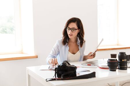 Image of a beautiful young pretty photographer woman in office sit at the table with camera and photos working.