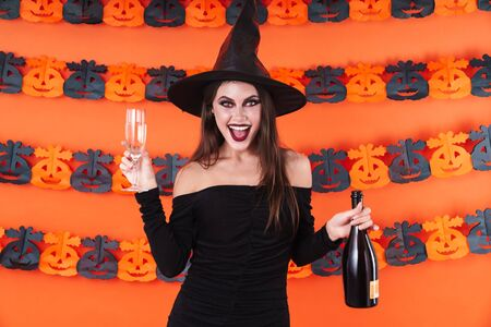 Image of young witch girl in black halloween costume holding champagne bottle and glass isolated over orange pumpkin wall Zdjęcie Seryjne