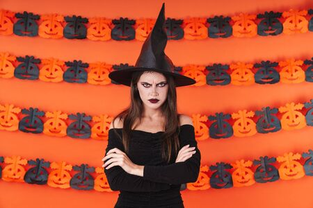 Image of angry witch girl in black halloween costume standing with arms crossed isolated over orange pumpkin wall