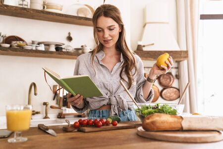 Image of young concentrated amazing pretty woman indoors at the kitchen cooking holding notebook and lemon. Stock Photo