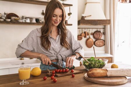 Image of young smiling concentrated happy positive cute beautiful woman indoors at the kitchen cooking.