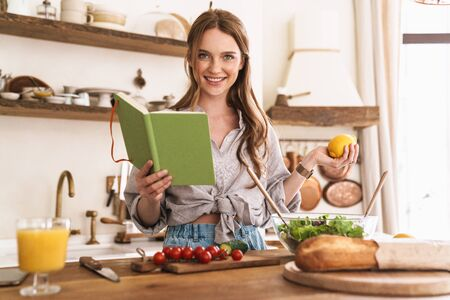 Image of young cute pretty woman indoors at the kitchen cooking holding notebook and lemon.