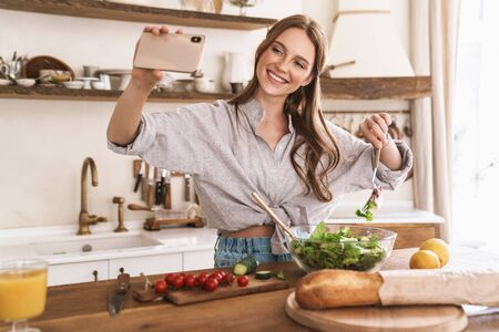 Image of young cheerful positive beautiful woman indoors at the kitchen cooking take selfie by mobile phone.