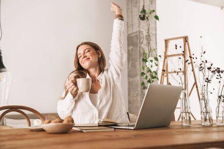Imagen de mujer de negocios joven pelirroja linda sentarse en el interior en la oficina estirando tomando café