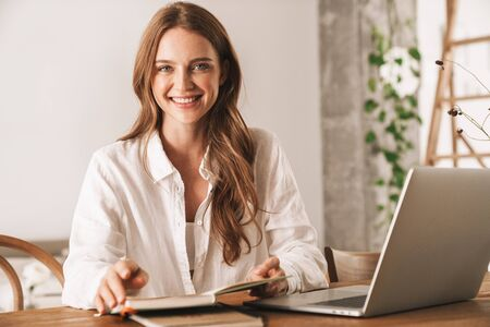 Photo of a cheerful positive young pretty business woman sit indoors in office using laptop computer holding notebook.