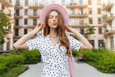 Image of a positive cute young redhead woman walking outdoors by street in dress blowing kisses. Stock Photo