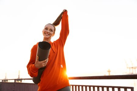 Cheerful sport lady in hoodie holding yoga mat and looking camera in sunrise outdoors Reklamní fotografie