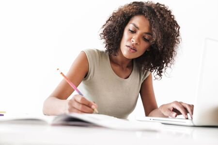 Attractive confident young african woman working with laptop computer and taking notes while sitting at the desk isolated over white background