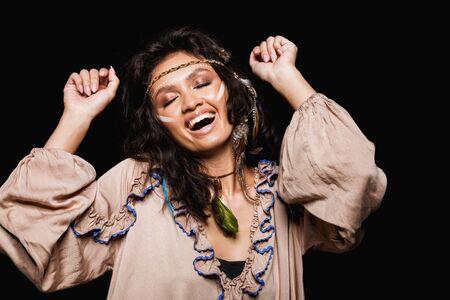 Porträt einer schönen fröhlichen jungen brünetten Frau, die Stammeskleidung und Accessoires trägt, die isoliert auf schwarzem Hintergrund steht und tanzt Standard-Bild