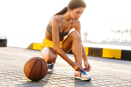 Image of young asian woman in sportive clothes tying her shoe laces while playing basketball against sea port