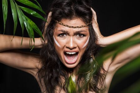 Beauty portrait of an attractive young brunette woman wearing tribal accessories posing with tropical leaves isolated over black background, screaming