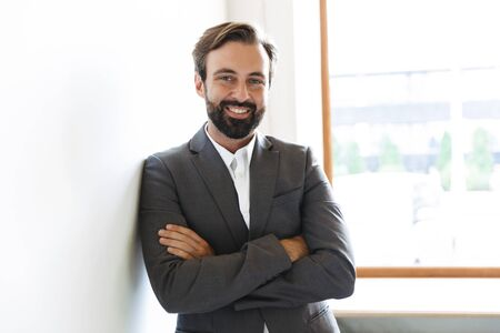 Photo of a handsome smiling positive bearded business man posing in office near window indoors.