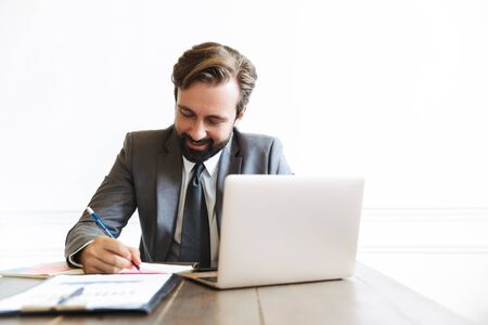 Image of happy handsome businessman wearing formal suit working at laptop in office while writing down notes