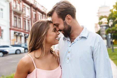 Cerca de una hermosa pareja feliz abrazando mientras está de pie en la calle de la ciudad, mirando el uno al otro