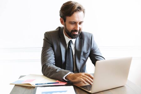 Image of a handsome young positive business man sitting in office using laptop computer working indoors.