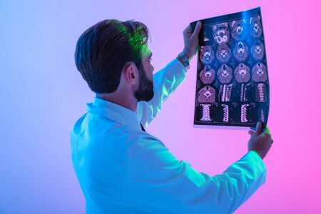 Side view portrait of a confident young man doctor wearing uniform standing isolated over pink-blue haze background, analyzing x-rays