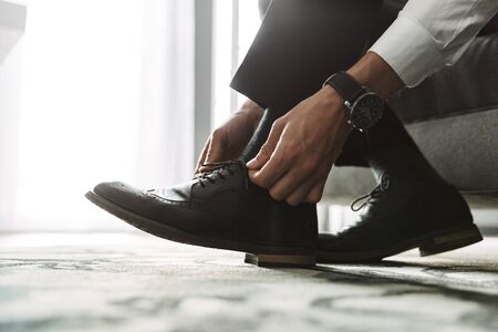 Cropped image closeup of successful man wearing formal suit tying his shoe laces while sitting on bed in hotel room during business trip