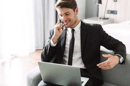 Image of a positive young businessman indoors at home using laptop computer talking by mobile phone.