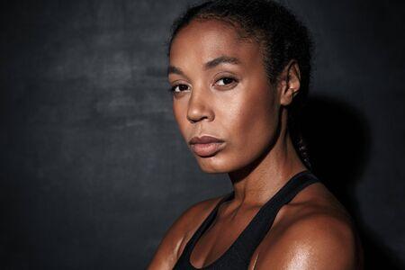 Gros plan de l'image de la jeune femme afro-américaine en vêtements de sport debout isolé sur fond noir Banque d'images