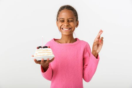 Image of excited african american girl holding piece of torte and making wish isolated over white background Banco de Imagens