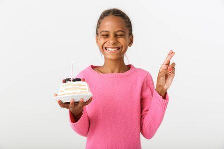 Imagen de una niña afroamericana emocionada sosteniendo un trozo de tarta y pidiendo deseo aislado sobre fondo blanco. Foto de archivo