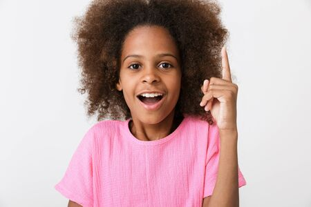 Cheerful little african girl wearing pink blouse standing isolated over white background, pointing fingers at copy space