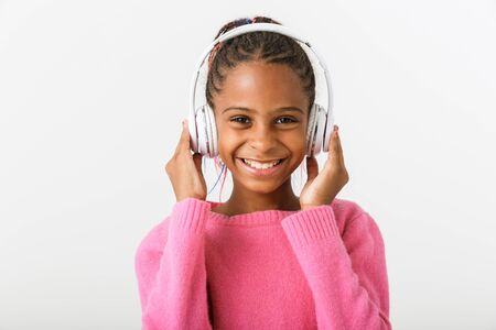 Image of pleased african american girl listening music with headphones while smiling isolated over white background 免版税图像