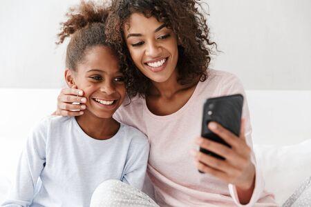 Bild einer zufriedenen Afroamerikanerin und ihrer kleinen Tochter, die zu Hause zusammen auf dem Sofa telefoniert Standard-Bild