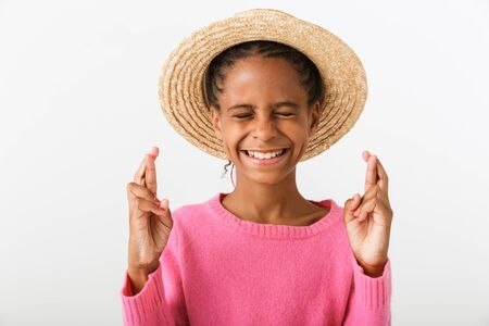 Image of smiling african american girl in straw hat holding fingers crossed isolated over white background Imagens