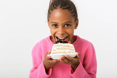 Image of smiling african american girl eating piece of torte while looking at camera isolated over white background