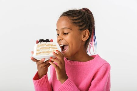 Image of happy african american girl holding and eating piece of torte isolated over white background Banco de Imagens