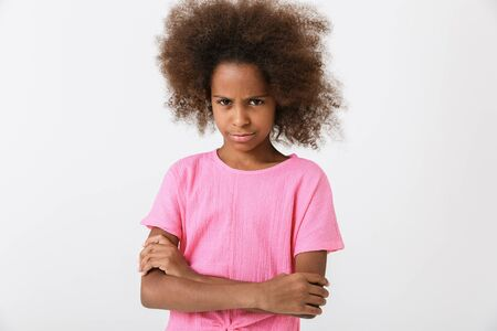 Upset little african girl wearing pink blouse standing isolated over white background, arms folded Stock Photo