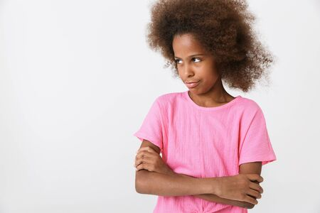 Upset little african girl wearing pink blouse standing isolated over white background, arms folded