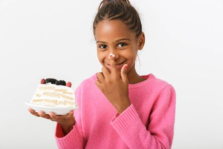 Image of amusing african american girl making fun with piece of torte isolated over white background 免版税图像