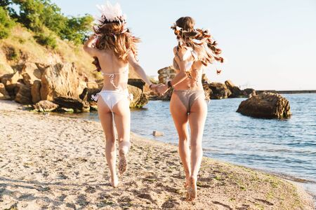 Image of lovely hippy girls in swimsuits holding hands and walking by seaside in morning